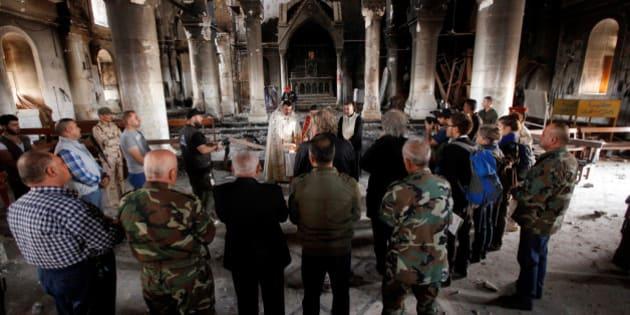Iraqi priests hold the first mass at the Grand Immaculate Church since it was recaptured from Islamic State in Qaraqosh, near Mosul, Iraq, November 2, 2016. REUTERS/Alaa Al-Marjani