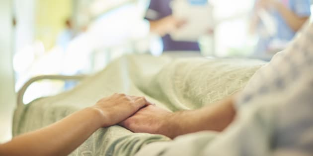 a hospital visitor's hand holds a patient's hand in bed of a hospital ward. In the blurred background a young nurse is chatting to the ward sister about the patient's care.