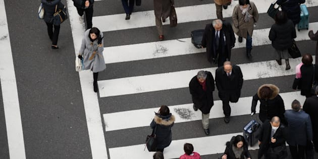 Pedestrians cross a road in Tokyo, Japan, on Friday, Feb. 24, 2017. Japan is responding to a government campaign to get the country's chronically overworked populace to leave the office by 3 p.m. on the last Friday of every month and go spend some cash. They call it Premium Friday. Photographer: Akio Kon/Bloomberg via Getty Images