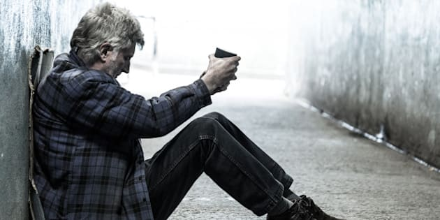 Homeless senior man with grey beard and grey hair sitting and begging alone in a subway tunnel. He is holding out a paper cup and begging for money. His head is bowed in shame and tiredness and hunger. He is wearing an old, tired blue lumberjack shirt, and he sits on a piece of cardboard. Horizontal colour image with plenty of room for copy space.
