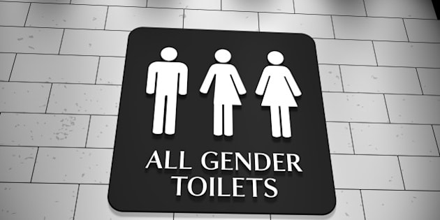 A sign on a wall for 'All Gender Toilets with symbols for men, trans and women. LGBT issue.