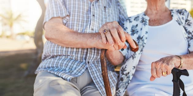 Close up of senior couple holding hands while sitting on the park bench together. Retired man and woman with walking cane. Focus on hands.