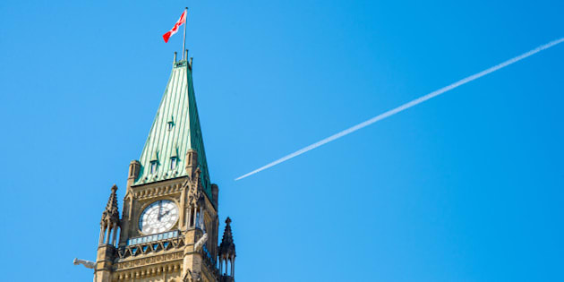 Canadian Parliament Peace tower in Ottawa, with a plane over the blue sky and a white smoke trail