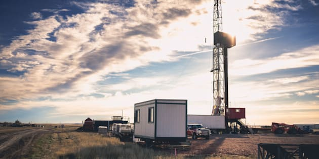Beautiful sky above a drilling Fracking Rig in the vast wild west of AmericaFracking Oil Well is conducting a fracking procedure to release trapped crude oil and natural gas to be refined and used as energy