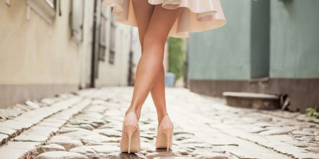 Woman wearing nude colored shoes and skirt; fashion shoot in old city