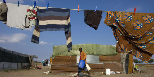 An African immigrant walks past a shack in a makeshift camp in the countryside near the village of Rignano Garganico, southern Italy, September 23, 2009. Every year thousands of immigrants, many of them from Africa, flock to the fields and orchards of southern Italy to eke out a living as seasonal workers picking grapes, olives, tomatoes and oranges. Broadly tolerated by authorities because of their role in the economy, they endure long hours of backbreaking work for as little as 15-20 euros ($22-$29) a day and live in squalid makeshift camps without running water or electricity. Picture taken September 23, 2009. REUTERS/Tony Gentile (ITALY POLITICS HEALTH EMPLOYMENT BUSINESS)