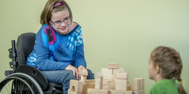 A young handicap girl is sitting in her wheelchair and is playing with other children - they are building towers using wooden blocks.