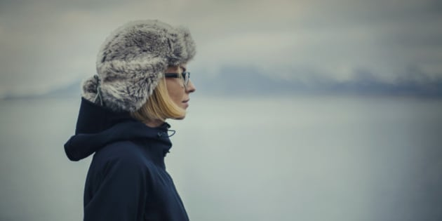 Young blond woman pensively looking at the blue of the ocean. She is wearing warm cap and black windproof jacket to protect herself from cold Islandic winter.