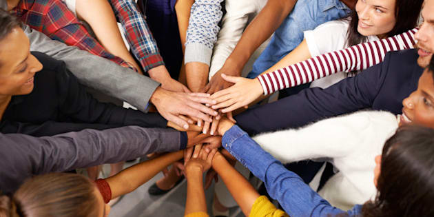 Shot of a diverse group of business people joining their hands in a symbol of unity