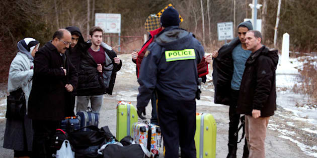 A group that claimed to be from Turkey is met by a Royal Canadian Mounted Police (RCMP) officer after they crossed the U.S.-Canada border illegally leading into Hemmingford, Quebec, Canada March 6, 2017.  REUTERS/Christinne Muschi