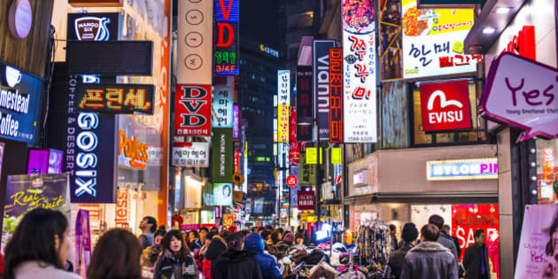 Seoul, South Korea - February 14, 2013: Crowds pass under the Myeong-Dong neon lights. The location is the premiere district for shopping in the city.