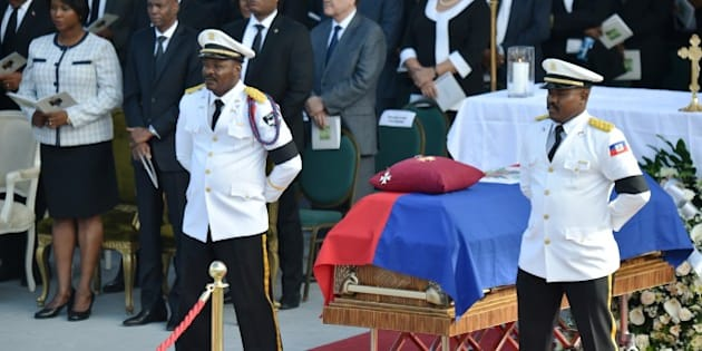 Police Officers from the National Palace stand next to the casket of former Haitian president Rene Preval during the State Funeral at the kioske Occide Jeanty, in Port-au-Prince, on March 11, 2017. 