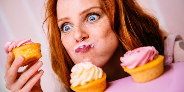 Young red head woman is enjoying cupcakes with a lot of enthusiasm