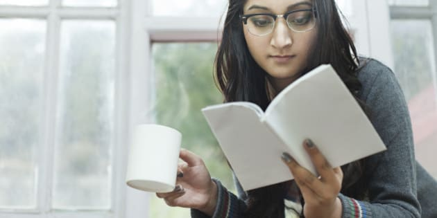 Indoor low angle image at day time in domestic room, near window of a beautiful, attractive Asian young woman reading a book while enjoying a mug of hot steaming coffee. One person, horizontal composition with selective focus and copy space.
