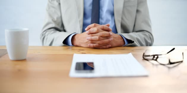 Cropped image of a businessman sitting with hands clasped and paperwork in front of him