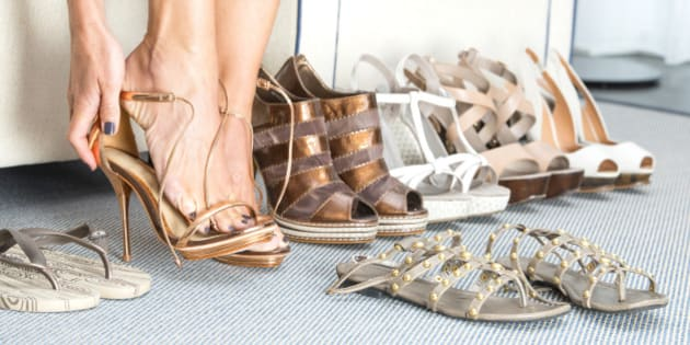 A woman is sitting on a sofa, in front of her several pairs of fashionable high heels shoes in different colors and styles. She is changing her shoes to a pair of sandals.
