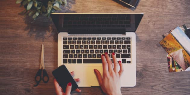 Vintage toned high angle image of a female photographer table workspace, a laptop, film cameras, hands typing on the keyboard.