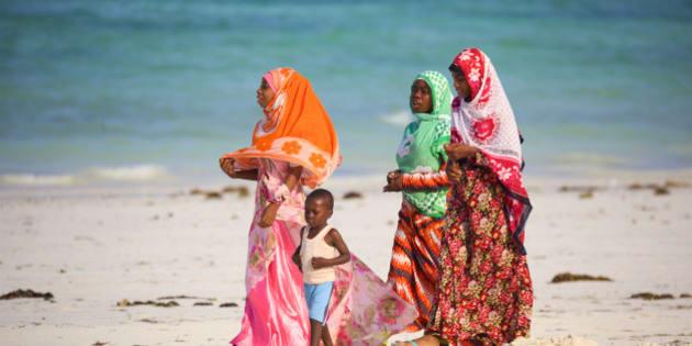 Kiwengwa Beach, Zanzibar, Tanzania - January 09, 2017: Local women with child walking along beach in traditional colorful clothes