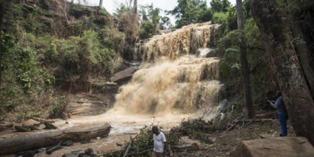 People walk in front of the Waterfalls in Kintampo on March 20, 2017, where 20 students lost their life in an accident a day before.  Ghana National Fire Service spokesman Prince Billy Anaglate said the 'unusual incident' happened on March 19 afternoon, when a group of high school students were swimming at the Kintampo waterfalls, a popular tourist destination in the Brong-Ahafo region. 18 students died at the scene while two others died in hospital, Anaglate said, adding that 11 more were receiving treatment, including one of the school administrators in charge of the trip.  / AFP PHOTO / CRISTINA ALDEHUELA        (Photo credit should read CRISTINA ALDEHUELA/AFP/Getty Images)