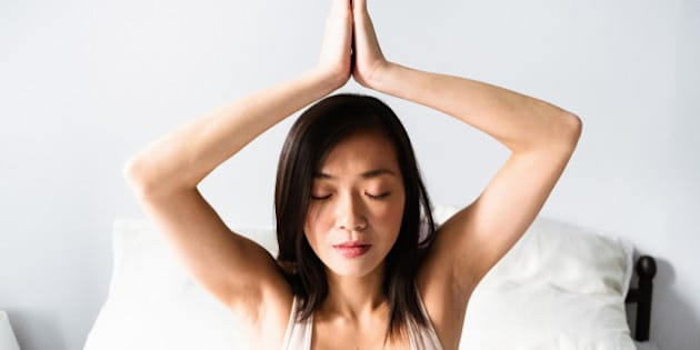 asian woman doing yoga in the bedroom