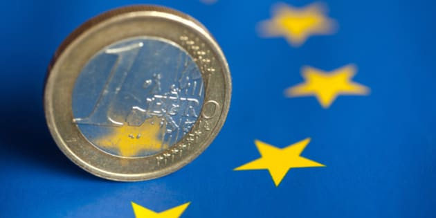 A one euro coin on flag of Europe.