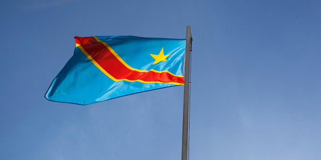 National flag of Congo on a flagpole in front of blue sky