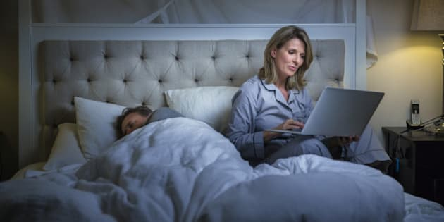 Mature woman using laptop while man sleeping on bed at home