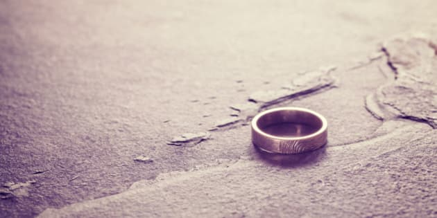 Vintage toned single weeding ring on stone background, conceptual picture.