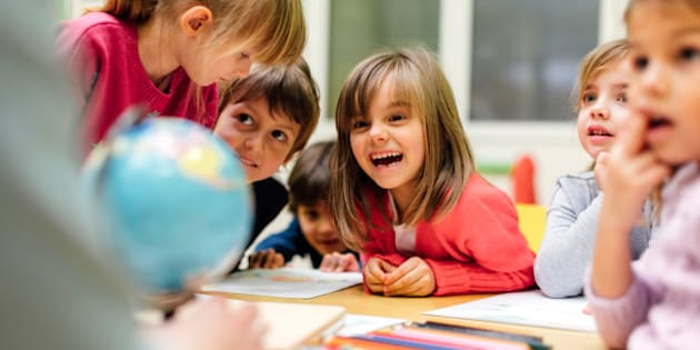Preschool teacher teaching her children about geography. Using globe and asking the questions. Children sitting by the table and listen teacher carefully. Models in this shot are part of real kindergarten group and their teacher.