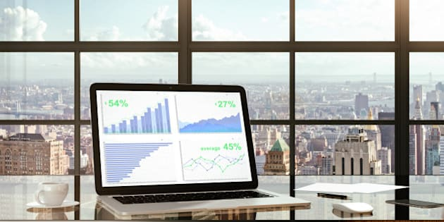 Financial statistics on laptop screen on glassy table in modern light office with megapolis city view