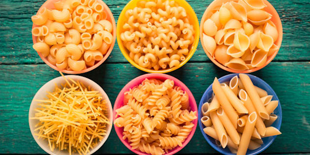 Various mix of pasta on wooden rustic background. Diet and food concept.