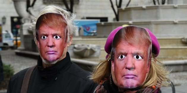 People wearing masks of US President Donald Trump take part in the 32nd Annual April Fools Day Parade in New York on April 1, 2017.  The theme for this years parade is MAKE RUSSIA GREAT AGAIN! The Grand Marshall will be a Donald Trump look-alike. The full parade was actually a April Fools' prank. / AFP PHOTO / TIMOTHY A. CLARY        (Photo credit should read TIMOTHY A. CLARY/AFP/Getty Images)