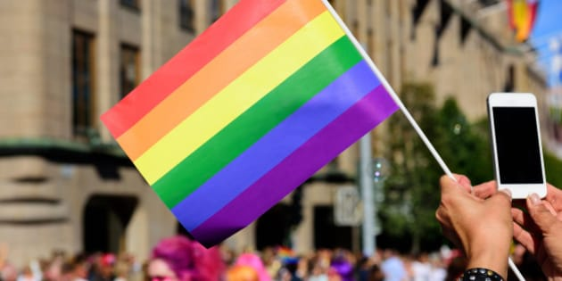 Pride flag and spectator taking pictures with mobile phone
