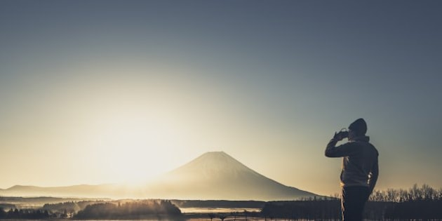 View of man drinking coffee in front of Mt. Fuji at sunrise.