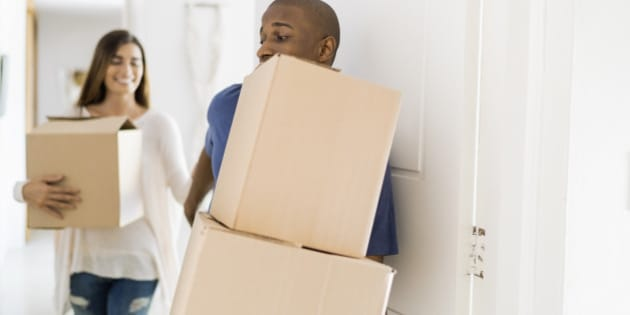 Young man and woman with cardboard boxes at doorway. Multi-ethnic couple are moving into new apartment. They are wearing casuals.