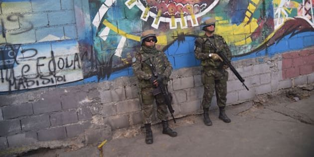 Brazilian military members from United Nations Stabilization Mission in Haiti (MINUSTAH) stand guard on a street near the Republic of Chile School in Port-au-Prince, March 27, 2017, as Chilean President Michelle Bachelet attends the inauguration of the facility.  / AFP PHOTO / HECTOR RETAMAL        (Photo credit should read HECTOR RETAMAL/AFP/Getty Images)
