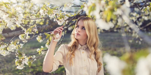 Portrait of a beautiful blonde enjoying the scents of a spring blossoms.