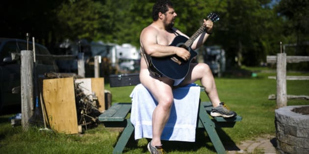 "A man plays a guitar at the Bare Oaks Family Naturist park in Sharon June 18, 2011. The International Naturist Federation says ""Naturism is a way of life in harmony with nature, characterized by the practice of communal nudity, with the intention of encouraging respect for oneself, respect for others and for the environment."" REUTERS/Mark Blinch (CANADA - Tags: SOCIETY)"