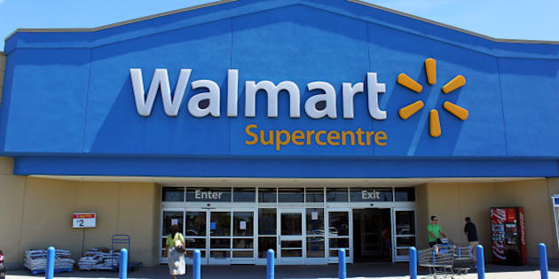 Etobicoke, Ontario, Canada - July 24, 2013: Customers in front of a Walmart Supercenter. Walmart is an American multinational retail corporation that runs chains of large discount department stores.