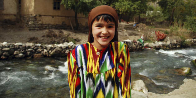 Tajikistan, Penjakent, portrait of local girl in traditional dress by the river