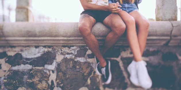 Cropped image of the legs of a hipster couple holding hands and sitting on a wall made of rough textured stone