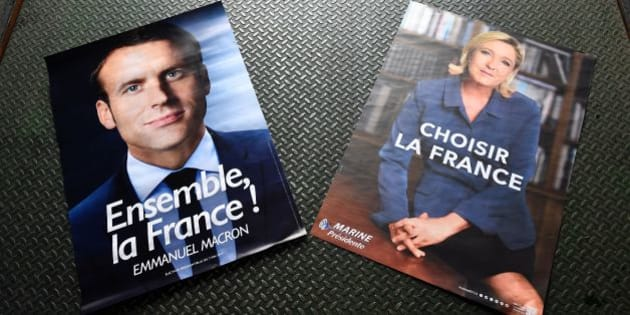 Electoral posters of French presidential election candidate for the En Marche ! movement Emmanuel Macron (L) and French presidential election candidate for the far-right Front National (FN) party Marine Le Pen (R) are displayed in a warehouse in Gonesse, north of Paris on April 26, 2017, ahead of the second round of the presidential election. / AFP PHOTO / Lionel BONAVENTURE        (Photo credit should read LIONEL BONAVENTURE/AFP/Getty Images)