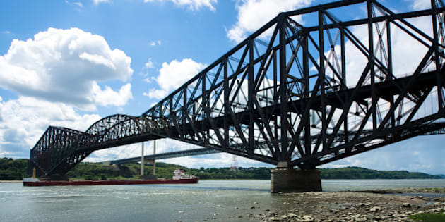 The Quebec Bridge is a combined road and rail bridge across the St. Lawrence River west of Quebec City. The Pierre Laporte Bridge (behind) is a road bridge over the St. Lawrence River, linking the cities of Quebec and Levis. It has the largest reach of all major Canadian suspension bridges.