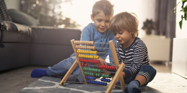 Little boy is helping his little brother to learn counting on abacus. Sunny day.
