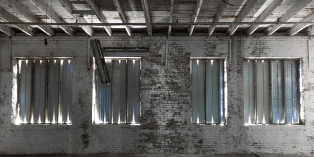 Dramatic lighting coming through boarded up windows in an abandoned building