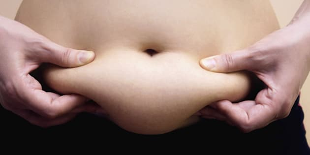 Obese women shows fat on her stomach, Photography