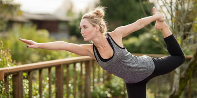 Beautiful young woman doing yoga on back porch in exercise clothes and yoga mat