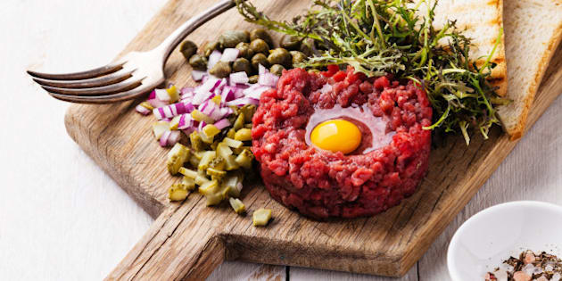 Beef tartare with capers and fresh onion on white wooden background