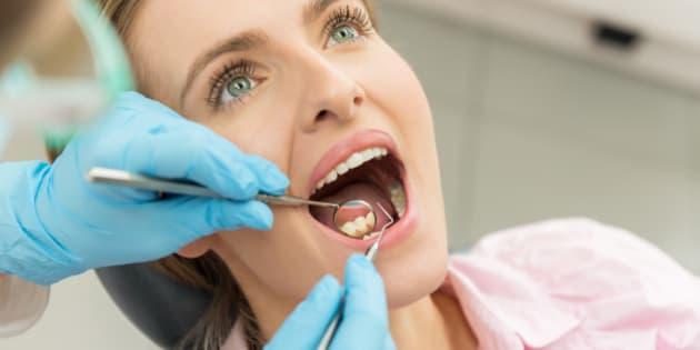 Horizontal color close-up headshot of beautiful woman having dental examination.