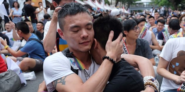 Same-sex activists hug outside the parliament in Taipei on May 24, 2017 as they celebrate the landmark decision paving the way for the island to become the first place in Asia to legalise gay marriage.